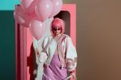 stylová holka v růžové paruka drží balónky a při pohledu na fotoaparát při stojící poblíž dekorativní box