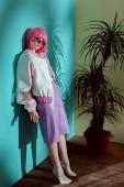 po celé délce pohled módní ženský model v růžové paruce naklánět na zdi a při pohledu na fotoaparát