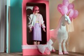 female model in pink wig standing in decorative box with bow
