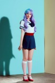 full length view of beautiful girl in bright wig and skirt standing and looking away in studio