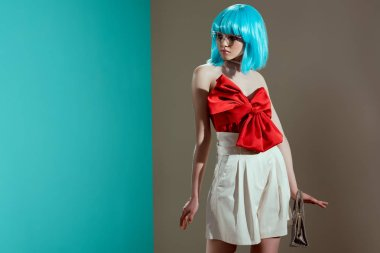 attractive young female model in blue wig and red bow looking away in studio