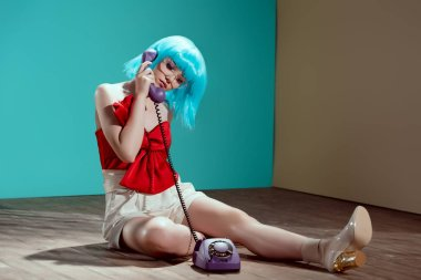 beautiful stylish female model sitting on floor and talking by rotary phone