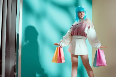 beautiful smiling young woman in blue wig holding paper bag and looking away