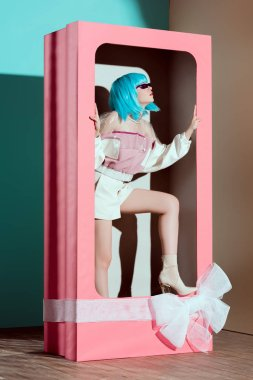 fashionable beautiful girl in blue wig posing in decorative pink box with bow