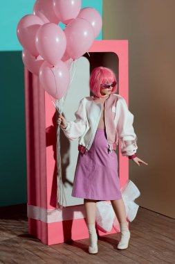 fashionable girl in pink wig holding balloons and looking away while standing near decorative box with bow