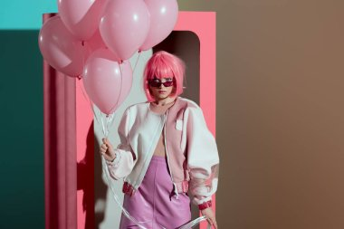 stylish girl in pink wig holding balloons and looking at camera while standing near decorative box