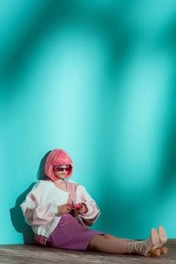 full length view of fashionable young female model in bright wig playing with pink gamepad