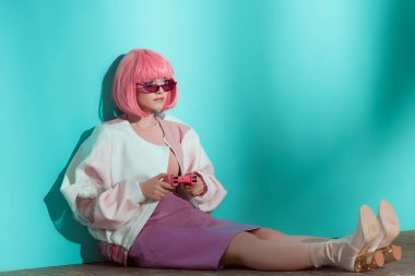 fashionable pretty girl in pink wig sitting on floor and using joystick