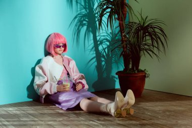 attractive fashionable girl in pink wig holding disposable cup with smoothie and sitting on floor