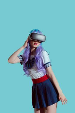 stylish girl in violet wig using virtual reality headset isolated on blue