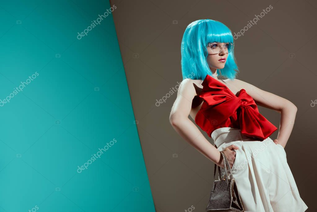 Low angle view of beautiful female model in blue wig standing with hands on waist and looking away stock vector