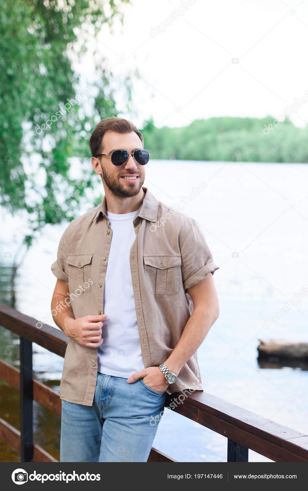 smiling handsome man leaning railing lake park stock photo