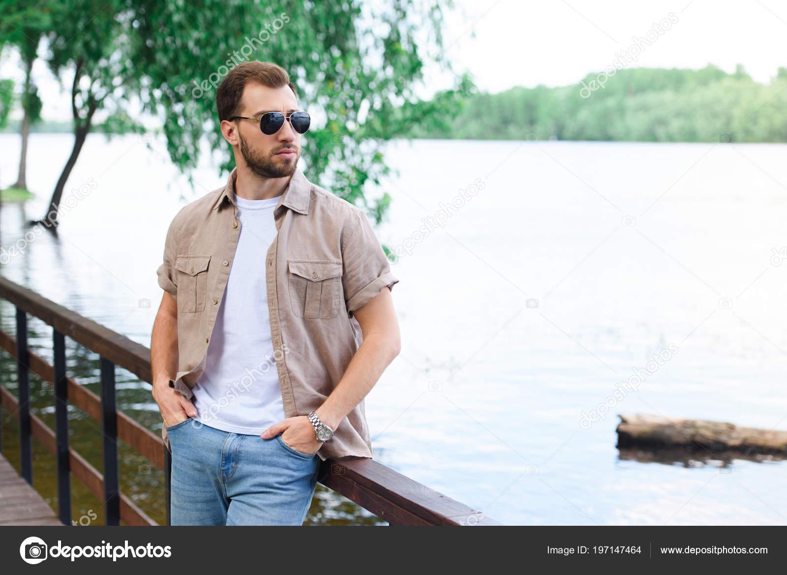 handsome man leaning railing lake park stock photo vitalikradko