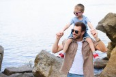 Fotografie smiling father holding son on shoulders and they looking away at park
