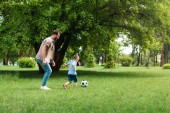 side view of father and son playing football at park