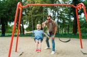 otec a syn baví na houpačce na hřišti v parku