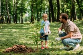 Fotografie father looking how son planting tree with shovel at park