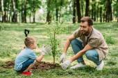 Šťastný otec a syn na výsadbu stromů v parku