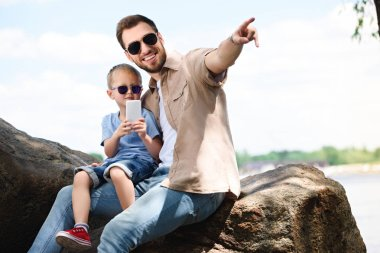 father pointing on something to son with smartphone at park