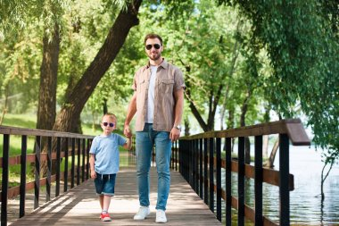 father and son in sunglasses holding hands and walking on bridge at park