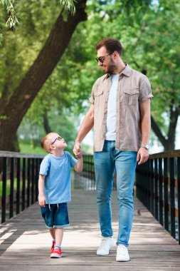 father and son holding hands and walking on bridge at park
