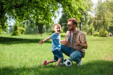 happy father and son with football ball at park
