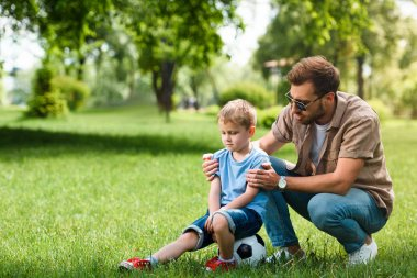 father hugging and supporting sad son after playing football at park