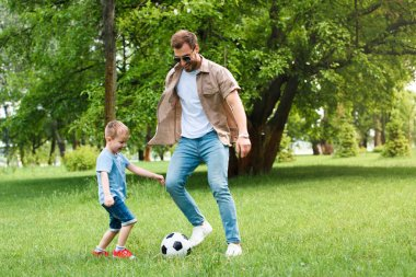 father and son having fun and playing football at park