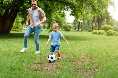 Father and son playing football at park stock vector