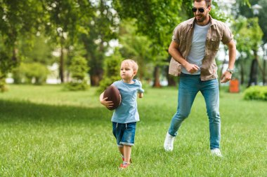 father and son running with american football ball at park