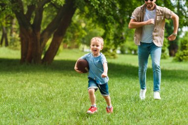 happy father and son running with american football ball at park