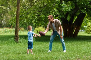 happy father and son playing american football at park