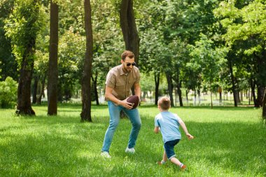 father and son playing american football together at park