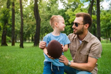 happy father and son looking at each other and holding american football ball at park