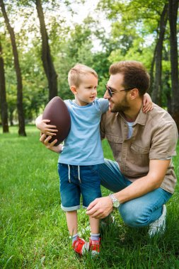 Father and son hugging and holding american football ball at park stock vector