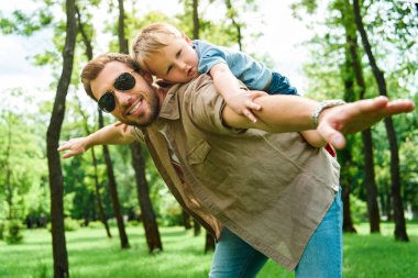 father giving piggy back to son at park