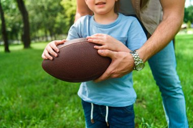 cropped image of father and son holding american football ball at park