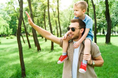 father waving hand to someone and holding son on shoulders at park