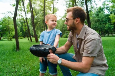 father wearing baseball glove on son hand at park