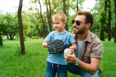 smiling father hugging son with baseball ball and glove at park