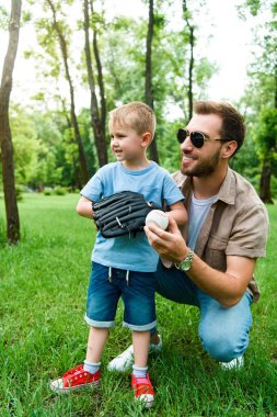 father hugging son with baseball ball and glove at park