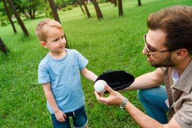 father giving son baseball ball in glove at park