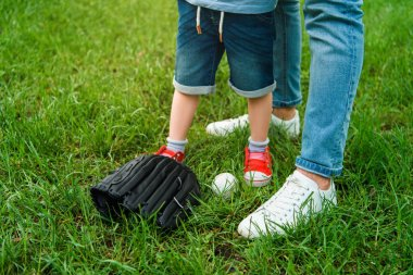 cropped image of father and son standing on grass near baseball ball and glove