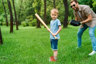 father and son playing baseball together at park