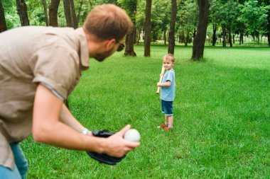 father and son playing baseball at park