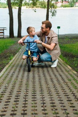 father and son with small bike looking at each other at park