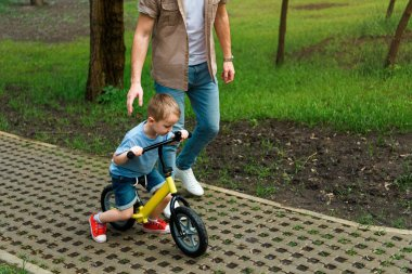 cropped image of father supporting son while he riding bicycle at park