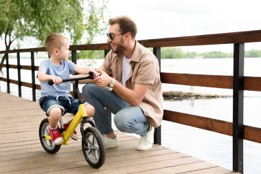 father teaching son riding bike on bridge at park