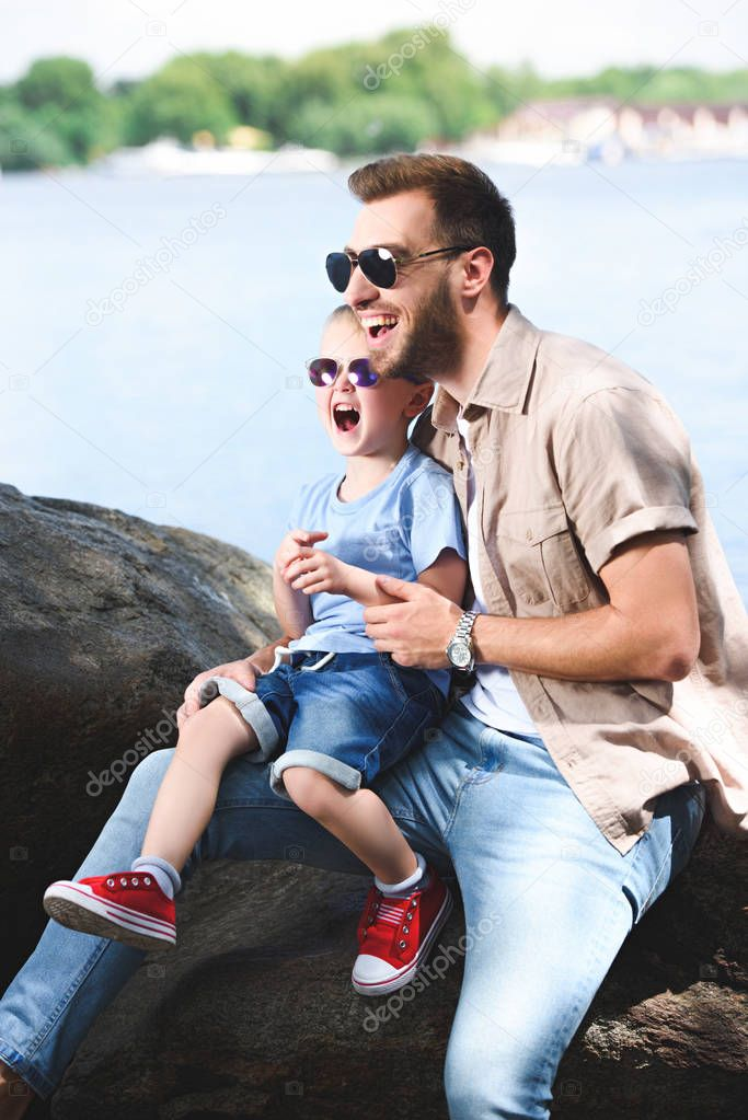laughing father and son looking away at park