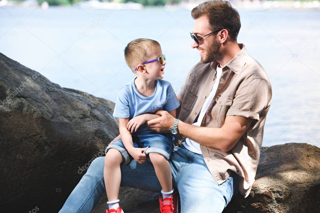 happy father and son looking at each other on stones at park